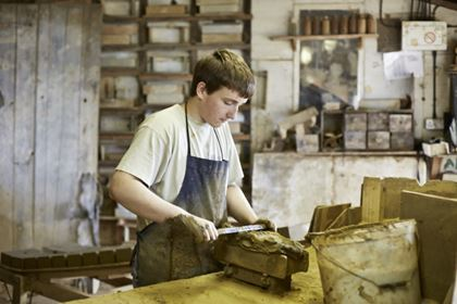 Young man making bricks at at traditional brickworks